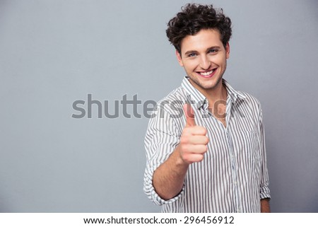Happy casual man showing thumb up over gray background and looking at camera - stock photo