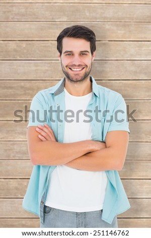 Happy casual man smiling at camera against wooden planks - stock photo