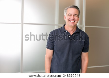 Happy casual mature business man in his office - stock photo