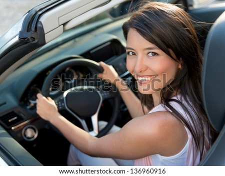 Happy casual woman driving a convertible car - stock photo