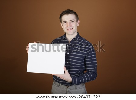 Happy casual young man holding a white board with blank space for copy standing in front of a brow background - stock photo