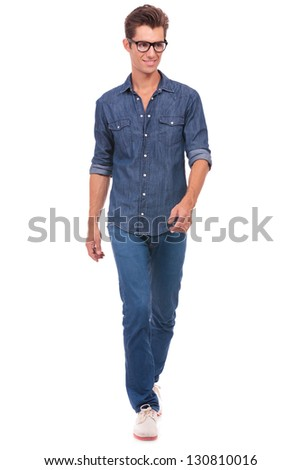 happy casual young man strolling towards the camera and looking in a different direction with a smile on his face. isolated on a white background - stock photo