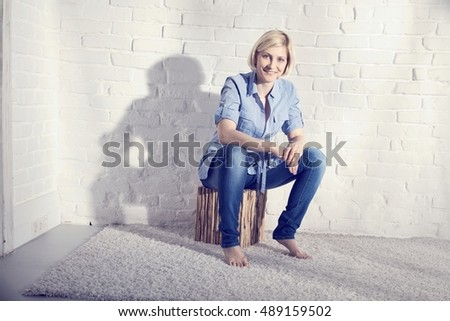Happy casual young woman sitting on stool front of white brick wall.