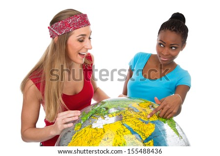 Happy Caucasian and African women posing with globe - stock photo