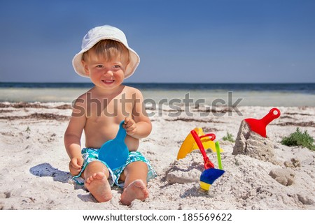 Happy caucasian baby (boy) is sitting and smiling at the beach. Child is playing with toys in summer day.  Travel concept. Outdoor. Close up. - stock photo