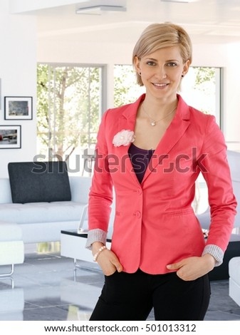 Happy caucasian blonde businesswoman standing at trendy home indoors. Smiling, hands in pocket, looking at camera, wearing woman business suit.