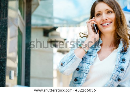 Happy caucasian brunette woman talking on phone outdoors - stock photo