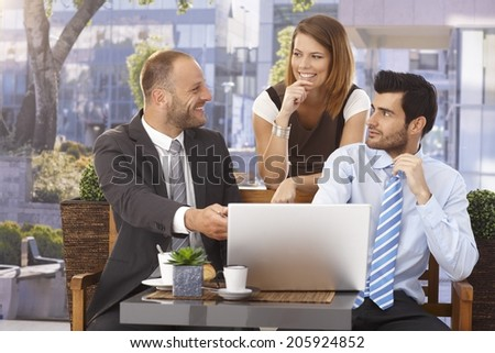 Happy caucasian businessman in suit explaining project on laptop at sunny outdoor cafeteria.
