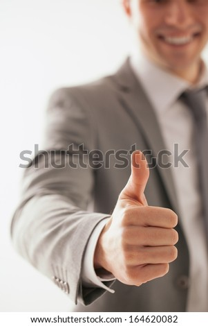 Happy Caucasian businessman showing thumbs up. - stock photo