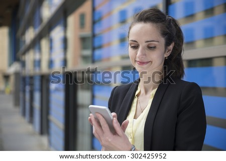 Happy Caucasian Businesswoman using her smart phone.  Business woman standing outside in modern city. - stock photo