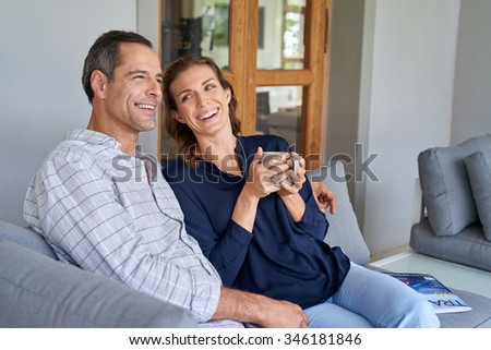 Happy Caucasian couple laughing and smiling enjoying coffee together outside sitting on terrace couch