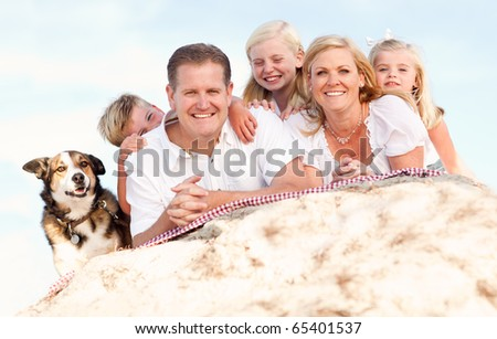 Happy Caucasian Family and Dog Portrait at the Beach One Sunny Afternoon. - stock photo