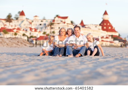 Happy Caucasian Family in Front of Hotel Del Coronado on a Sunny Afternoon. - stock photo