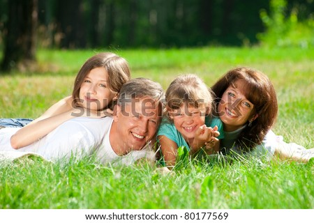 Happy caucasian family lying down on the grass in park