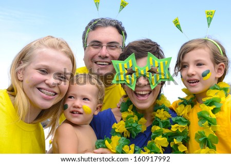 Happy caucasian family of brazilian soccer fans commemorating victory together - stock photo