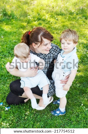 Happy caucasian family of three: Young mother and two little sibling boys in summer park, Europe - stock photo