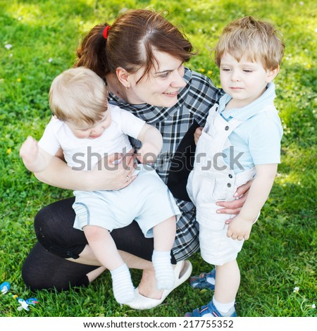 Happy caucasian family of three: Young mother and two little sibling boys in summer park, Europe.  Square size. - stock photo
