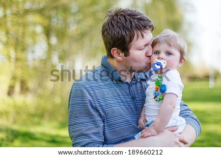 Happy caucasian family of two: Young father and baby boy in spring forest on sunny warm day - stock photo