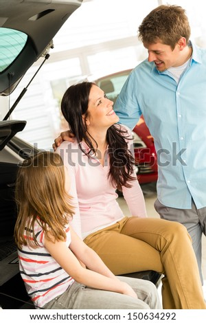 Happy Caucasian family sitting in new car's boot - stock photo