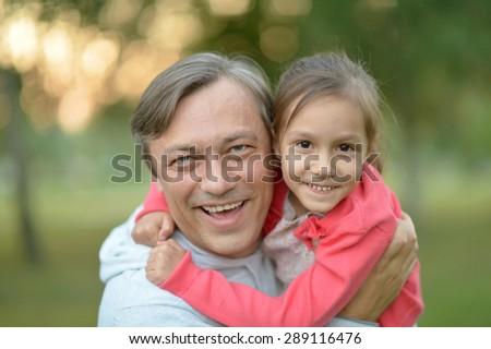 Happy Caucasian father holding his daughter in his arms - stock photo