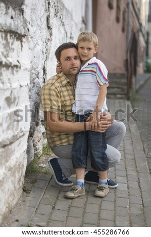 Happy caucasian father squatted down and hugs his son with love at the street of old town in the evening sunshine