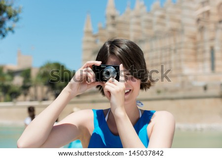 Happy Caucasian female tourist taking pictures in Palma de Mallorca, Spain, Europe, with an ancient fortress in the background - stock photo