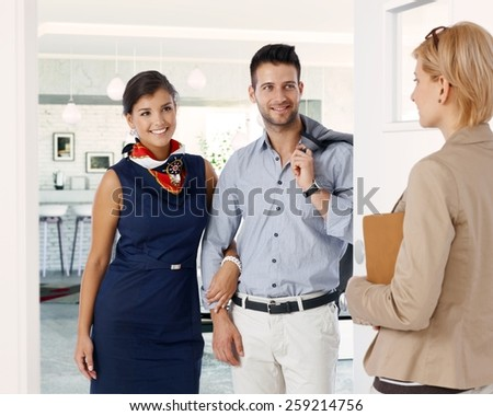 Happy caucasian formal couple meeting businesswoman at home. Smiling, standing in doorway, hand in hand, holding hands. - stock photo