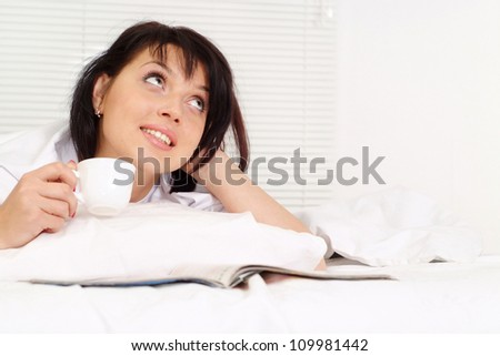 Happy Caucasian girl lying in bed on a light background
