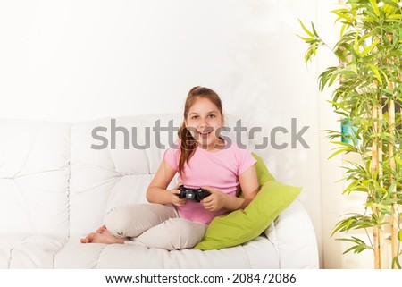 Happy Caucasian girl playing video games holding game controller sitting on the coach in living room - stock photo