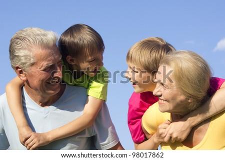 Happy Caucasian happy grandparents with grandchildren with fool on the street - stock photo