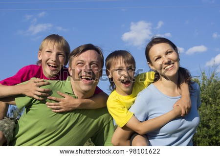 Happy Caucasian hsppy mother and father together with his sons play the fool on the street