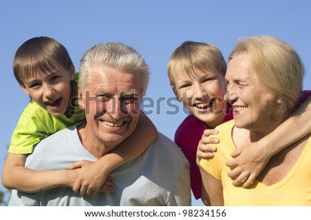Happy Caucasian joy grandparents with grandchildren with fool on the street