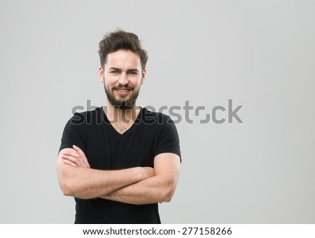happy caucasian man standing with crossed arms against his chest, on grey background. copy space available - stock photo