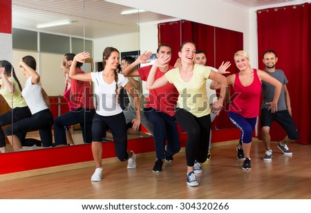 Happy caucasian people dancing in a sports hall on a choreography lesson - stock photo