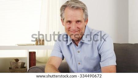 Happy caucasian senior man smiling and sitting in living room - stock photo