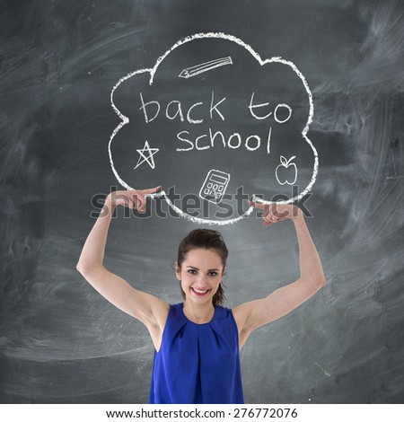 Happy Caucasian Woman pointing at 'Back to School' concept hand drawn on chalkboard. - stock photo