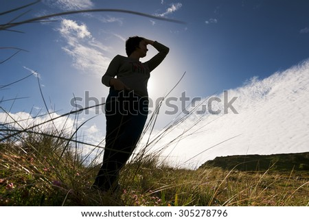 happy caucasian woman silhouette in the field with blue sky and  white clouds - stock photo
