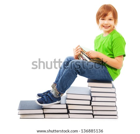 Happy Caucasian 9 years old boy in green shirt sitting on stairs made of stack of books, holding stack of textbooks, isolated on white - stock photo