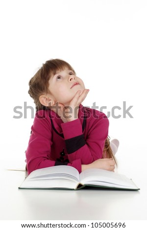Happy Caucasian young girl lying with a book on a white background