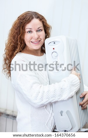 Happy Caucasian young woman embracing new oil heater in domestic room - stock photo