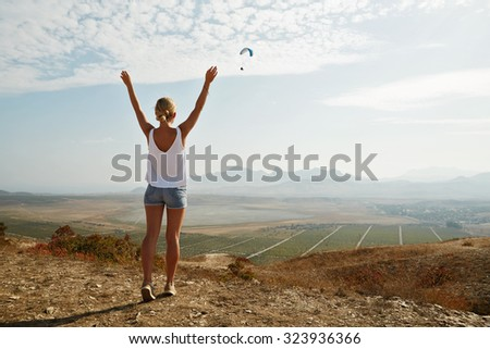 Happy celebrating winning success woman at sunset or sunrise standing elated with arms raised up above her head in celebration of having reached mountain top summit goal during hiking travel trek