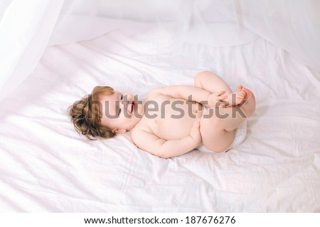 Happy charming baby on the bed home