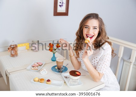 Happy charming young woman eating small cakes and drinking latte in cafe - stock photo