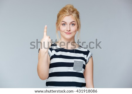 Happy charming young woman showing one finger and pointing up over white background - stock photo