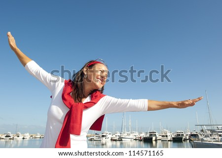 Happy cheerful and attractive looking senior woman enjoying active retirement with holiday at ocean marina, isolated with sailing boats and blue sky as background and copy space.