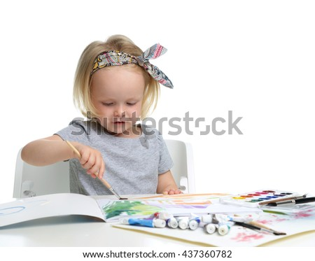 Happy cheerful baby girl child drawing with brush in album with painting tools isolated on a white background - stock photo