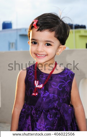 Happy cheerful beautiful / cute smiling Indian baby girl in bright purple velvet /  trendy silk dress, North India, Indian daughter joyful young naughty looks. people. infant face. fashion, necklace - stock photo