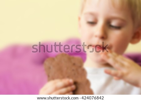 Happy cheerful boy eating a chocolate candy bar holding hands, smearing the face, blurred background for - stock photo