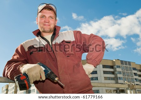 Happy cheerful Builder laborer in work wear with screwdriver machine - stock photo