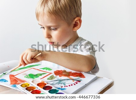 Happy cheerful child draws paints a southpaw in the album, using a variety of drawing tools. Creativity concept of a boy holding a brush, a happy childhood,   Selective focus - stock photo